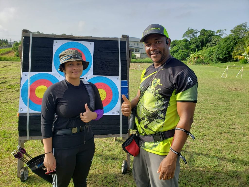Head coach of South Arrows Archery Club Sherwin Francis with a student