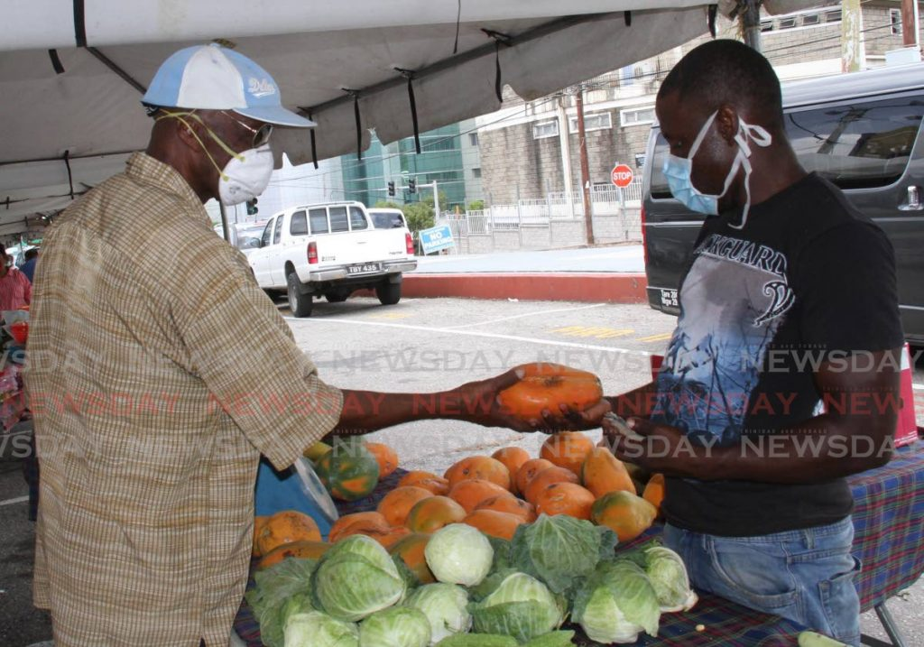 In this May 8, 2020 file photo an elderly man buys paw paw from a vendor at the Namdevco market, San Fernando. They both wore masks. The Health Minister on Saturday again appealed to the public to wear masks properly. PHOTO BY VAHSTI SINGH  -