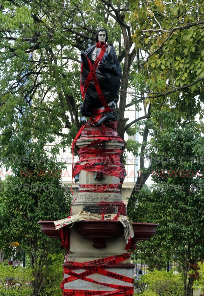 In this June 20, 2020 file photo, the Christopher Columbus statute, in the square named after him in Port of Spain, is defaced in paint and caution tape. PHOTO BY SUREASH CHOLAI -