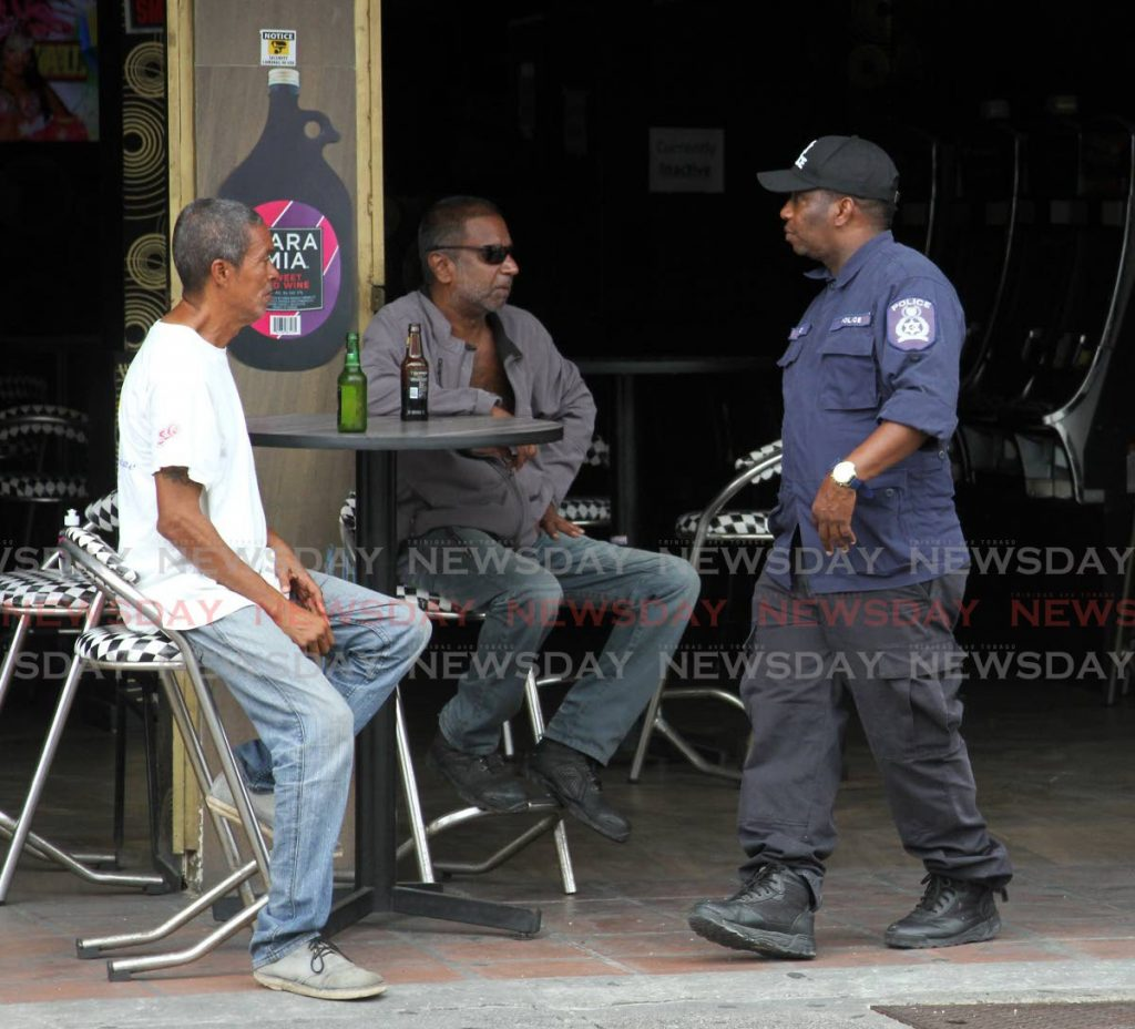 In this file photo a policeman walks past men drinking at a bar on Western Main Road, St James on June 22. - Angelo Marcelle