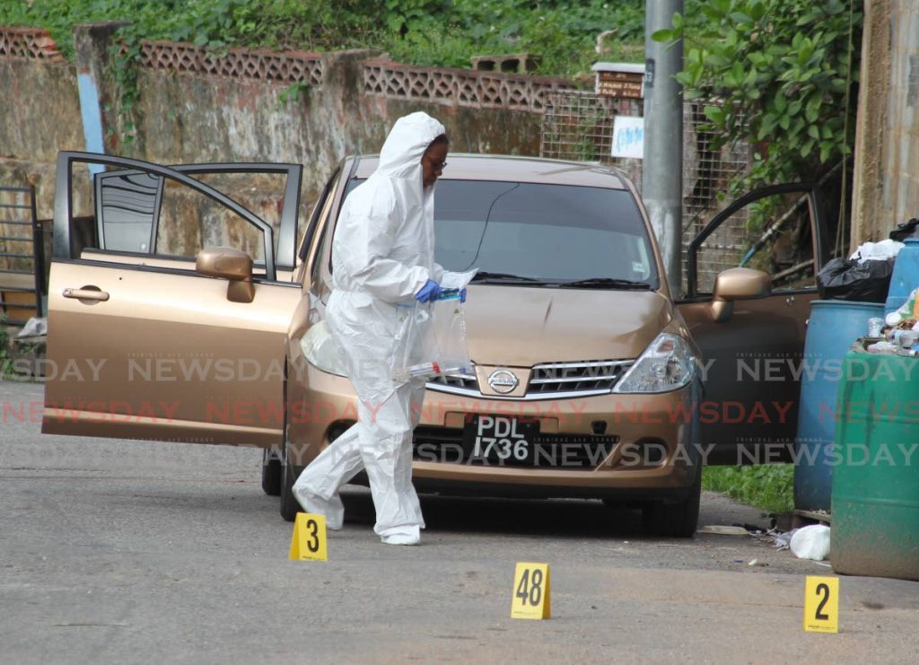 A crime scene investigator gathers evidence at Second Caledonia, Morvant where police shot and killed three men on June 27. PHOTO BY ROGER JACOB -