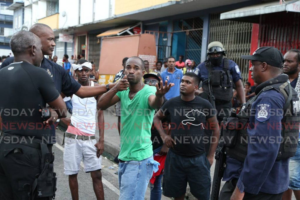 A protester while talking to police on George Street, Port of Spain on Wednesday, simulates the action of police as they shot tear gas at protesters during an earlier march on Frederick Street. - Jeff K. Mayers
