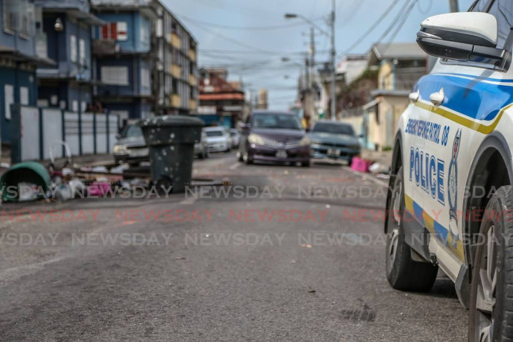 Motorists are forced to manoeuvre around debris that partially blocks Upper George Street, Port of Spain, on Thursday. The debris was placed by residents in protest over police killings last Saturday. - Jeff Mayers