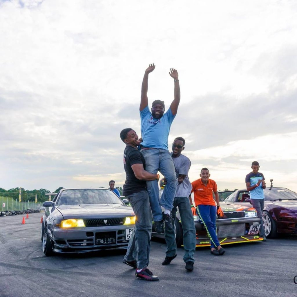Kerry 'Drift King' Philip (centre) is held up by his friends Roger Hutcheon (left) and Devon Bartholomew. Photo by Conrad Baird.