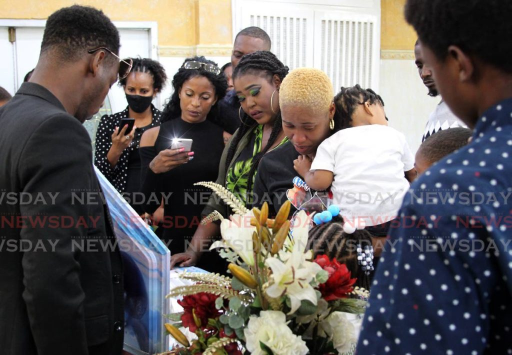Maysonia Thomas, companion of Israel Moses Clinton, holding the younger of their two children, cries as she, relatives and friends view his body Simpson's Funeral Home, Eastern Main Road, Laventille on Monday. - ROGER JACOB