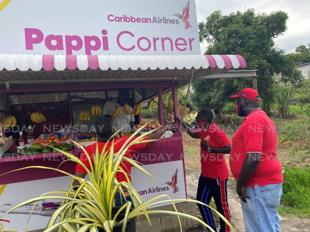 Former Point Fortin MP Edmund Dillon (left) and Point Fortin mayor and PNM candidate Kennedy Richards Jr (centre) speak with a man in a fruit stall during a walkabout in Gonzales Village, Guapo, Point Fortin on July 6. While employees should be guided by company policy on electioneering in the workplace, owners of small and micro businesses may be freer to show their support for a candidate or party. - FILE PHOTO