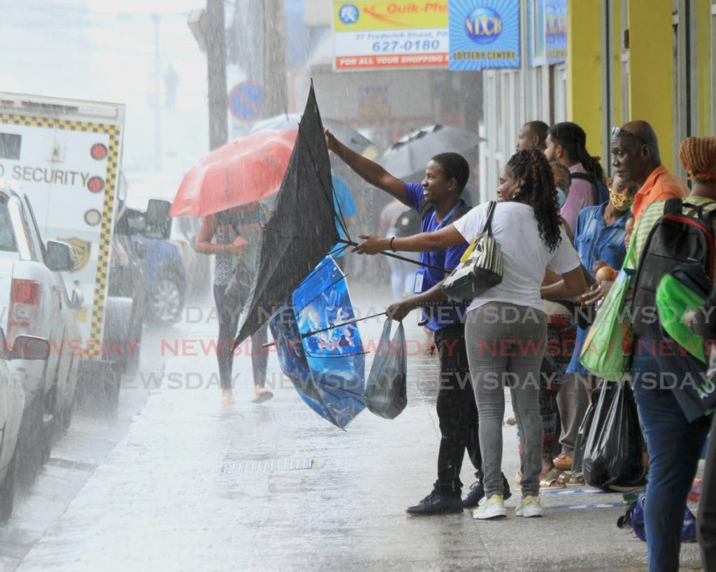 In this July 7, 2020 file photo a man helps a woman to fix her umbrella blown open by strong gust during heavy rain in Port of Spain. As of July 25, Tobago is on a warning and Trinidad on a bad level alert for Tropical Storm Gonzalo. - Ayanna Kinsale