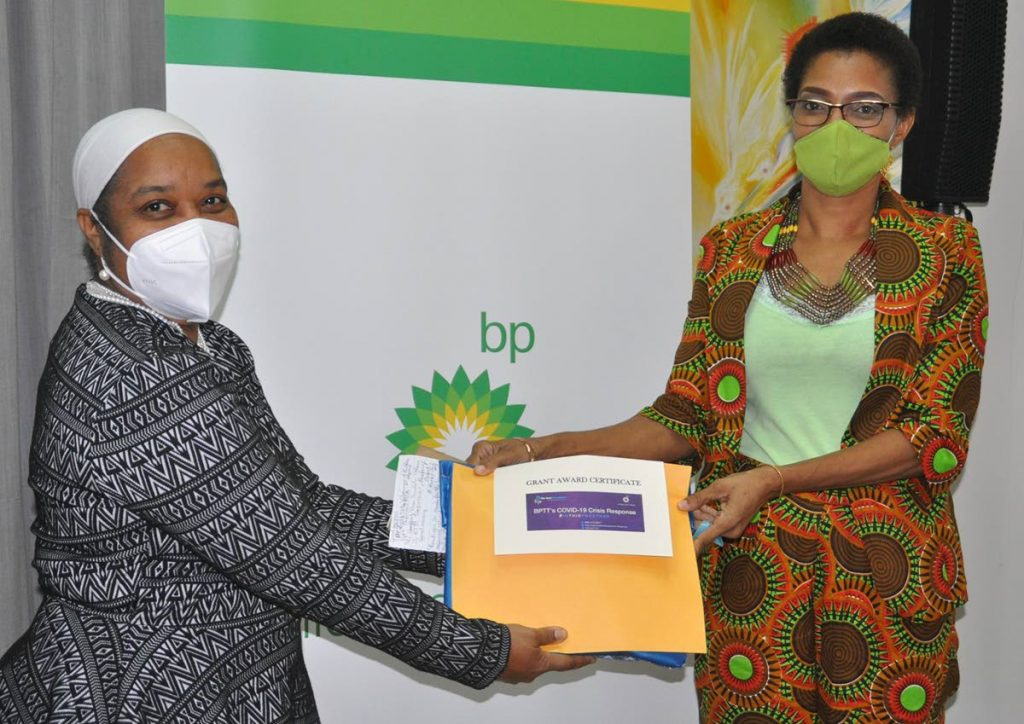 Marcia Belgrove, left, director of the Rose Foundation presents a laptop to Desrie Slinger-Griffith, founder of the Shield Us From Gang Violence Personalised Learning School.  -