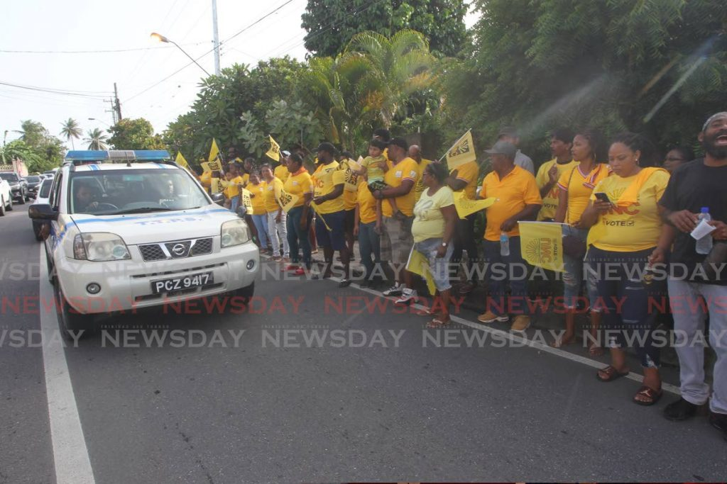 Police drive past UNC supporters gathered for the opening of the campaign office for candidtae Michelle Benjamin in St Mary's Village, Moruga on July 8. PHOTO BY LINCOLN HOLDER -