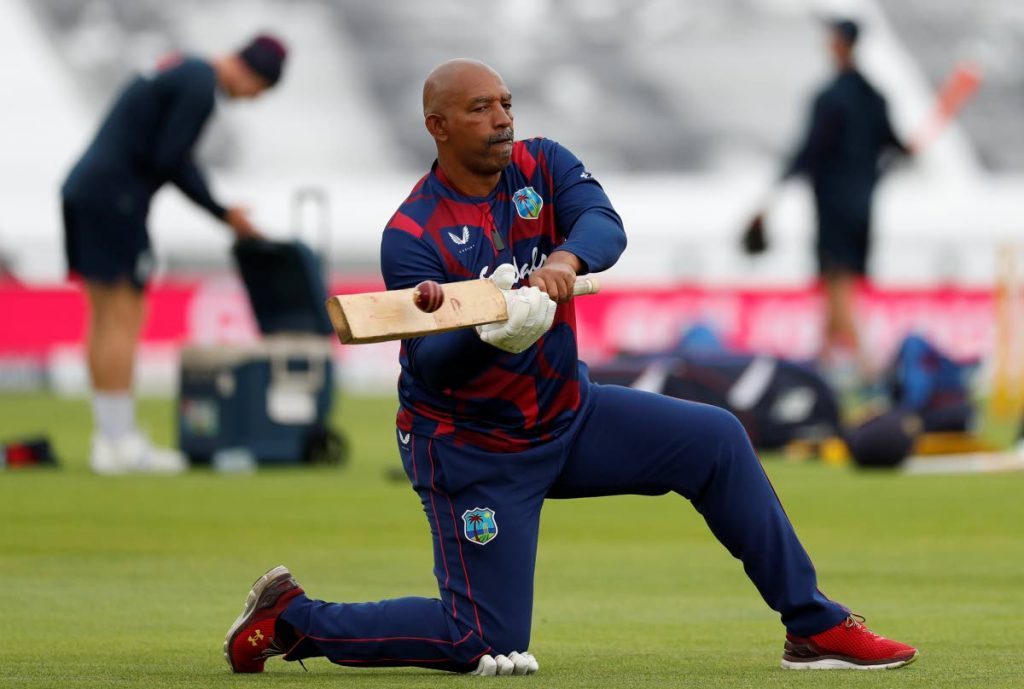 In this photo taken on Thursday, West Indies' coach Phil Simmons helps players train before the start of play on the second day of the first Test between England and West Indies, at the Ageas Bowl in Southampton, England. via AP -