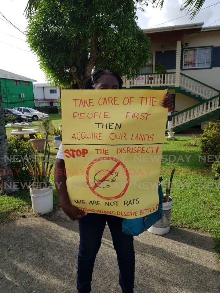 ANGRY: A resident displays a placard during the protest in Canaan/Bon Accord last week.  PHOTO BY KINNESHA GEORGE-HARRY -