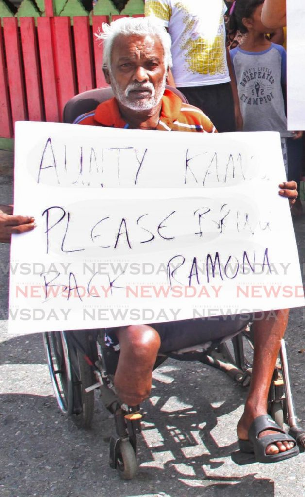 A resident of Bank Village, Carapichaima, protests on Sunday for Opposition Leader Kamla Persad Bissessar to bring back the outgoing MP Ramona Ramdial.  - Vashti Singh