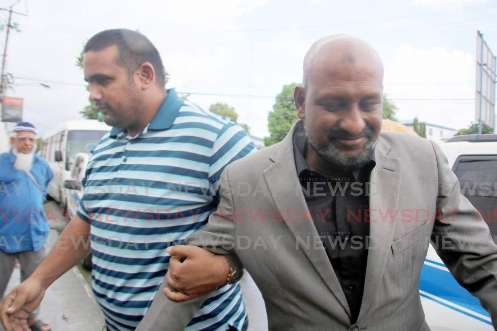 In this October 31, 2017 file photo businessman Inshan Ishmael is led to the Chaguanas Magistrate's Court by PC Khan on three charges, including gun possession. Ishmael was freed of the charges on Tuesday, July 14, 2020. PHOTO BY VASHTI SINGH