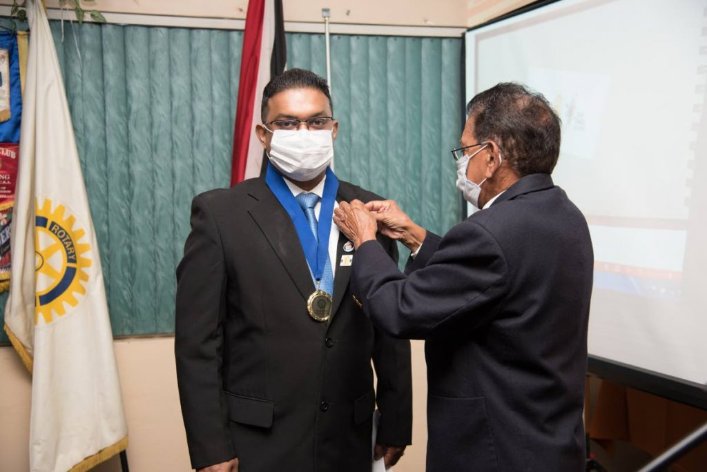Past president of the Princes Town Rotary Club Jamir Ousman hands over the presidential chain and pins to the new president Rishi Ramlogan. -