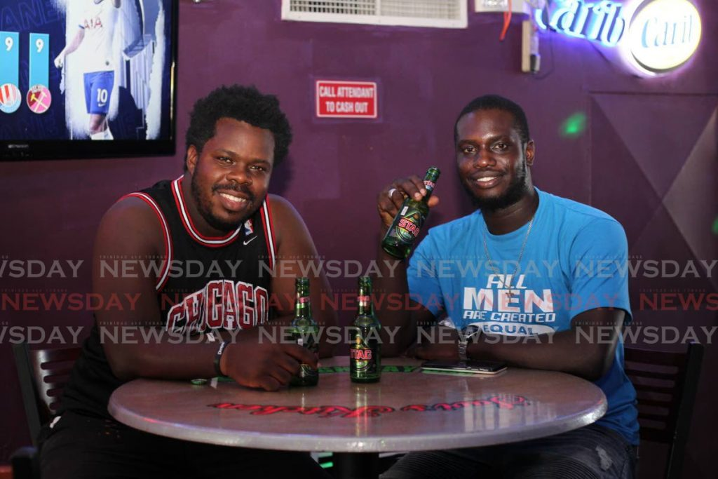 Kyle St Hillaire and Zoneal Denoon enjoy a round of beers at Kash Highway Bar, Boundary Road Extension, Aranguez on Saturday. The Health Minister announced bars can once more open until 10 pm from Monday. PHOTOS BY ROGER JACOB -