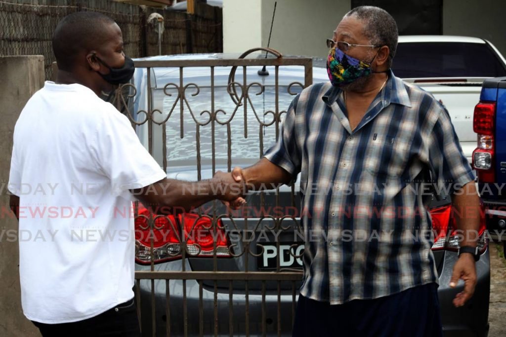 Foster Cummings, PNM candidate for La Horquetta Talparo, shakes hands with a La Horquetta resident during a unity walk on Sunday. - ROGER JACOB