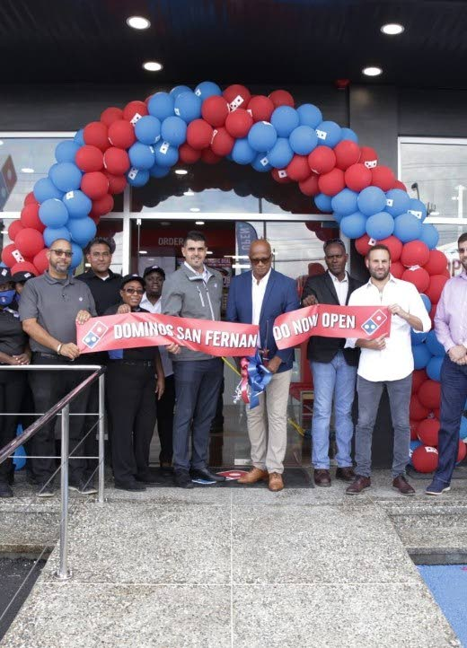 OPENED FOR BUSINESS: San Fernando Mayor Junia Regrello and local franchise holder for Domino's Pizza Daniel Fakoory, at Regrello's left in the photo, cut the ribbon to open the Gulf View outlet of the pizzeria last Friday.  -
