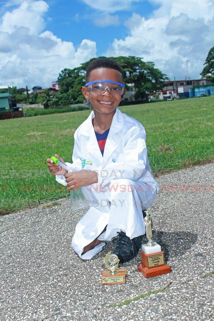 Kassidy Primus is all smiles in his lab coat, and with his Erlenmeyer flask and two science awards from Progressive Private Institution at Skinner Park, San Fernando. He also wore his football uniform under his coat to go play a game.  -