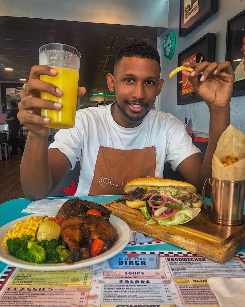 Rakeem Parpit enjoys a Philly cheesesteak sandwich, fries, half roasted chicken, mac n cheese and sautéed broccoli at Blue Star Diner in Maraval. Photo Courtesy Rakeem Parpit -