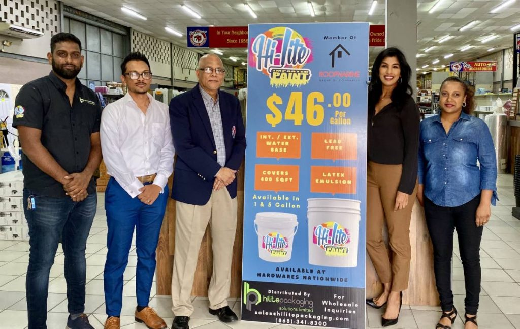 Ish Roopnarine, left, of Roopnarine's Hardware, and staff members with TTCB president Azim Bassarath, third from left, at the presentation of the Hi-lite paint for the National Cricket Centre. -