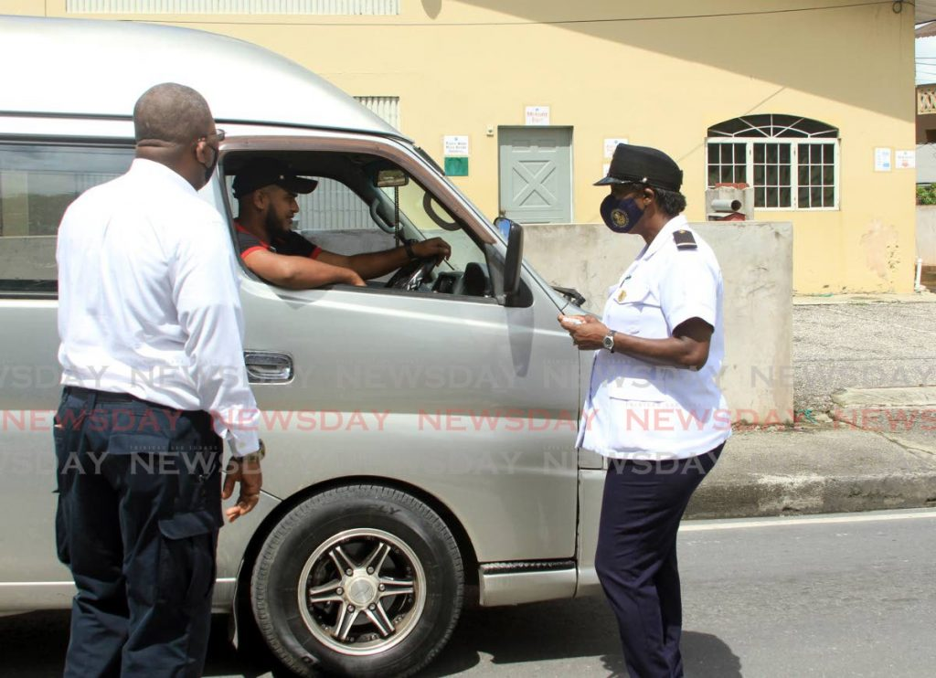 Transport officers speak with a driver on the Eastern Main Road in Guaico, Sangre Grande on Friday.  PHOTO BY AYANNA KINSALE -