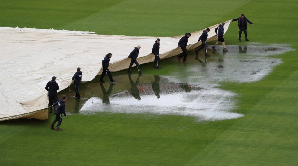 Groundsmen pull on the covers as rain delayed start of the play on the fourth day of the third Test match between England and West Indies at Old Trafford in Manchester, England, on Monday. (AP PHOTO) -