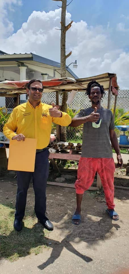 Dr Rishad Seecheran gives thumbs up with a Kelly Village resident duing his walkabout on July 17. Seecheran entered politics after seeing the difficulty faced by many in TT.  - Photo taken from UNC Caroni East Facebook page