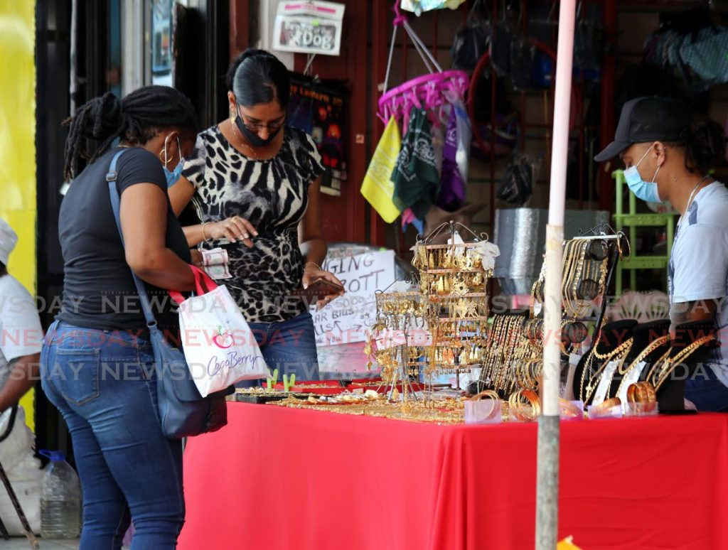 RESPONSIBLE: This roadside fashion vendor, right, and her customers did the responsible thing and wore masks on Charlotte Street in Port of Spain on Monday.  - Sureash Cholai