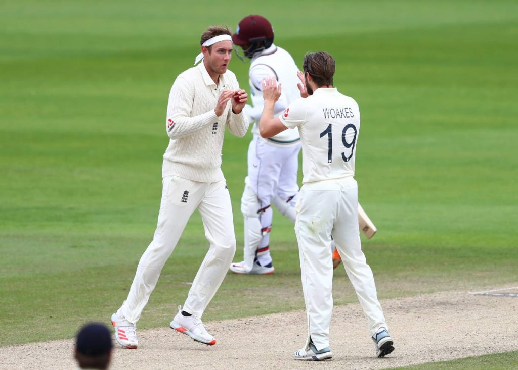 England's Stuart Broad (left) celebrates with teammate Chris Woakes (right), after taking the catch to dismiss West Indies' Shai Hope (centre), during the fifth day of the third Test match between England and West Indies at Old Trafford in Manchester, England, on Tuesday. (AP PHOTO) -
