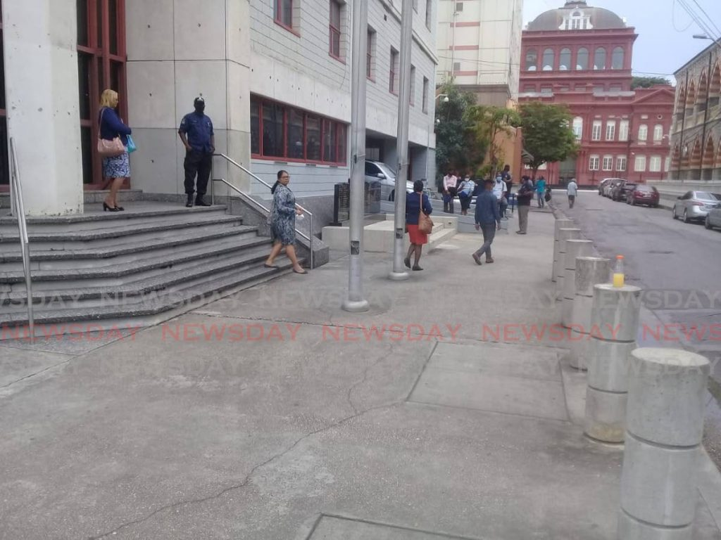 Workers at the Police Administration Building on Sackville Street in Port of Spain leave the building on Tuesday. - SHANE SUPERVILLE