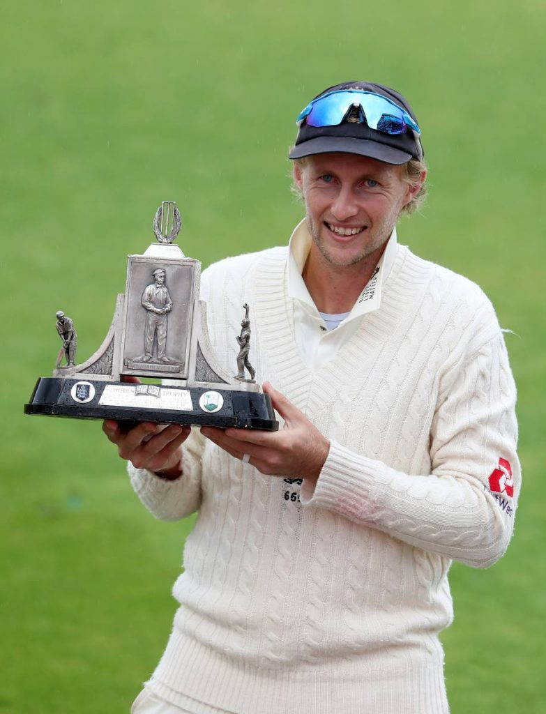 England's captain Joe Root poses with the Wisden Trophy after their win on the fifth day of the third Test match between England and West Indies at Old Trafford in Manchester, England, on Tuesday. (AP PHOTO) -