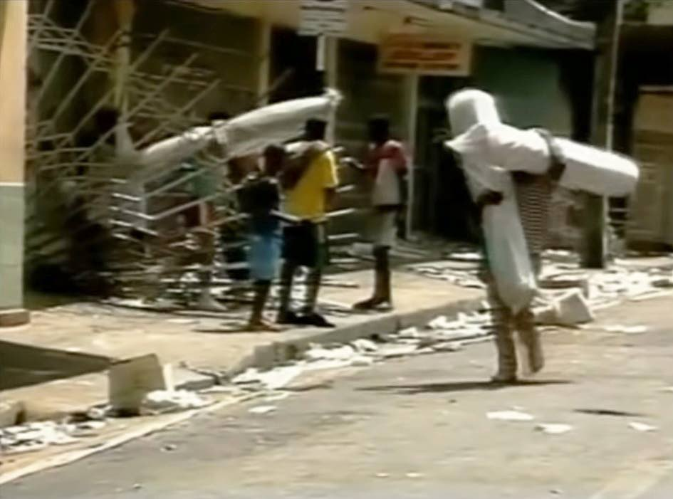 LOOTING:  Screen grab from a YouTube video of a documentary shows people leaving with items looted from businessplaces in downtown Port of Spain at the height of the attempted coup 30 years ago.  -