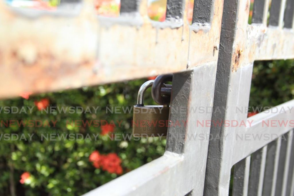 LOCKED: The front gate of the St Augustine South Government Primary School was locked on Wednesday as the school remain closed for sanitisation after reports that a student may have been exposed to a covid19 patient.  - ROGER JACOB
