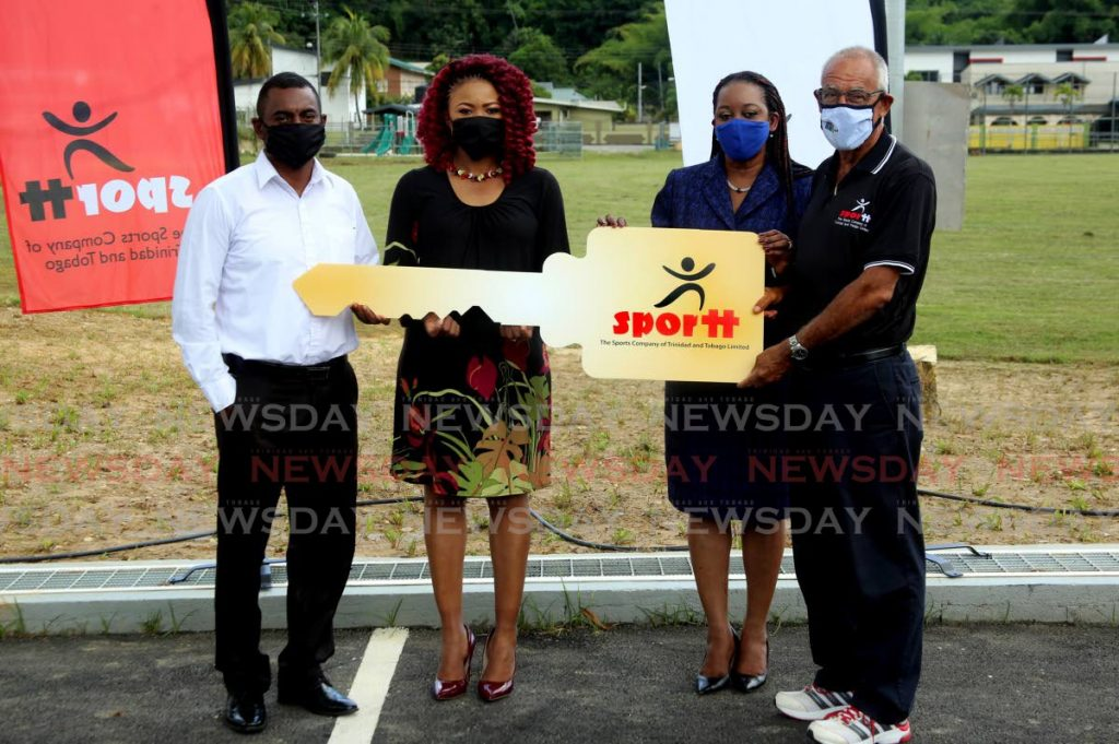 Dr Nyan Gadsby-Dolly, former St Ann's East MP (second from left) hands over the keys of the newly refurbished Brian Lara Recreation Ground to councillor Eldon Coker (left) of the San Juan/Laventille Regional Corporation, on behalf of the Sports Company of TT (SporTT). Also in photo are SporTT chairman Douglas Camacho (right) and Claire Davidson-Williams, deputy permanent secretary of the Ministry of Sport and Youth Affairs. PHOTO BY SUREASH CHOLAI. - SUREASH CHOLAI