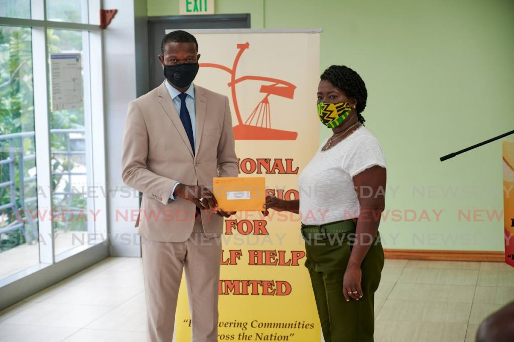 Dianne Saunders, right, collects her grant from National Self Help Commission Ltd CEO Elroy Julien at a ceremony on Monday in Scarborough.  - LEEANDRO NORAY