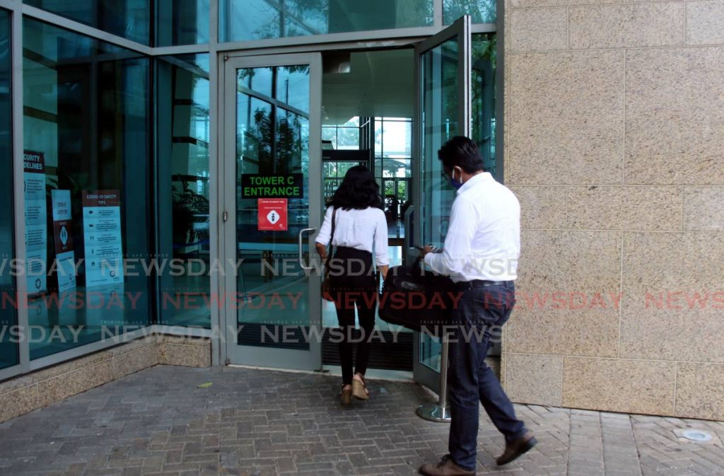 Employees enter Tower C at the International Waterfront, Port of Spain on August 5, where the staff in several departments of the Ministry of the Attorney General and Legal Affairs were sent home when it was reported that the relative of a worker contracted covid19. PHOTO BY SUREASH CHOLAI -