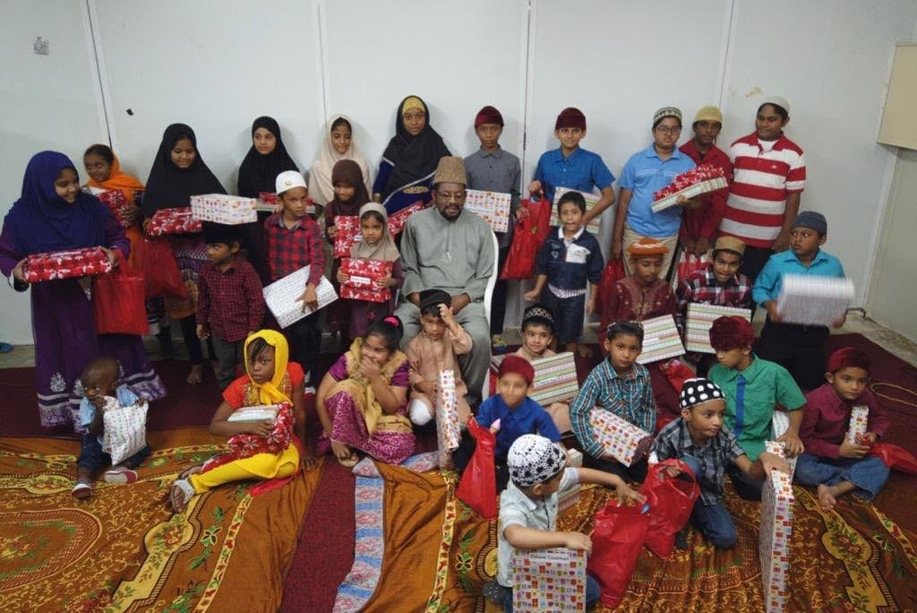 Amir Maulana Ibrahim Bin Yaqub, centre, sits among a group of children who received presents after a special children's day programme in January at the Ahmadiyya Muslim Community's Preysal headquarters in January. PHOTO COURTESY THE AHMADIYYA MUSLIM COMMUNITY -