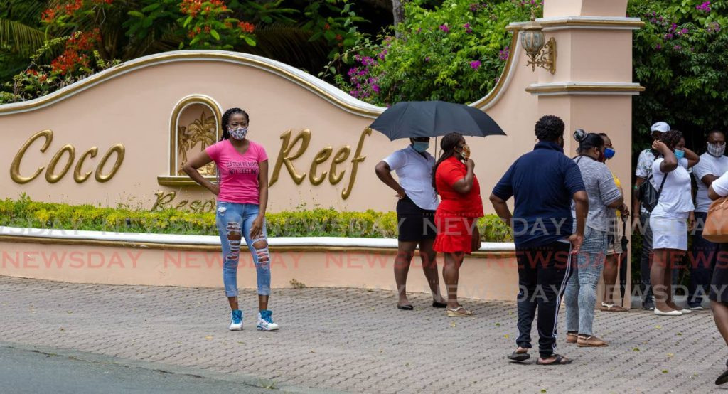 Coco Reef Resort & Spa employees gather at the entrance to the hotel on Wednesday to protest a decision by management to send them home without pay for two more months. PHOTO BY DAVID REID  -