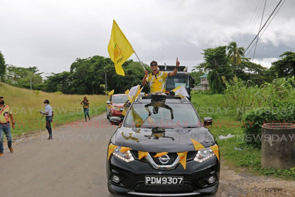 Princes Town candidate for the UNC Barry Padarath waves a flag while being driven through the constituency in a motorcade on Friday morning.   - Marvin Hamilton