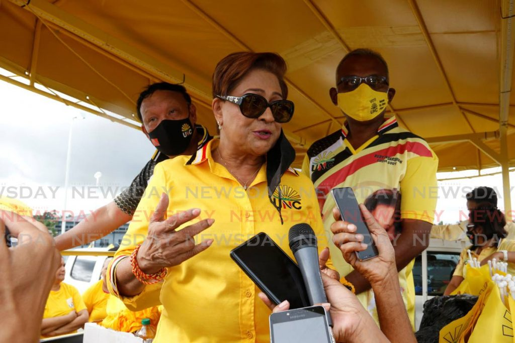 UNC political leader Kamla Persad-Bissessar speaks with reporters during a motorcade in San Fernando on Friday. - Marvin Hamilton