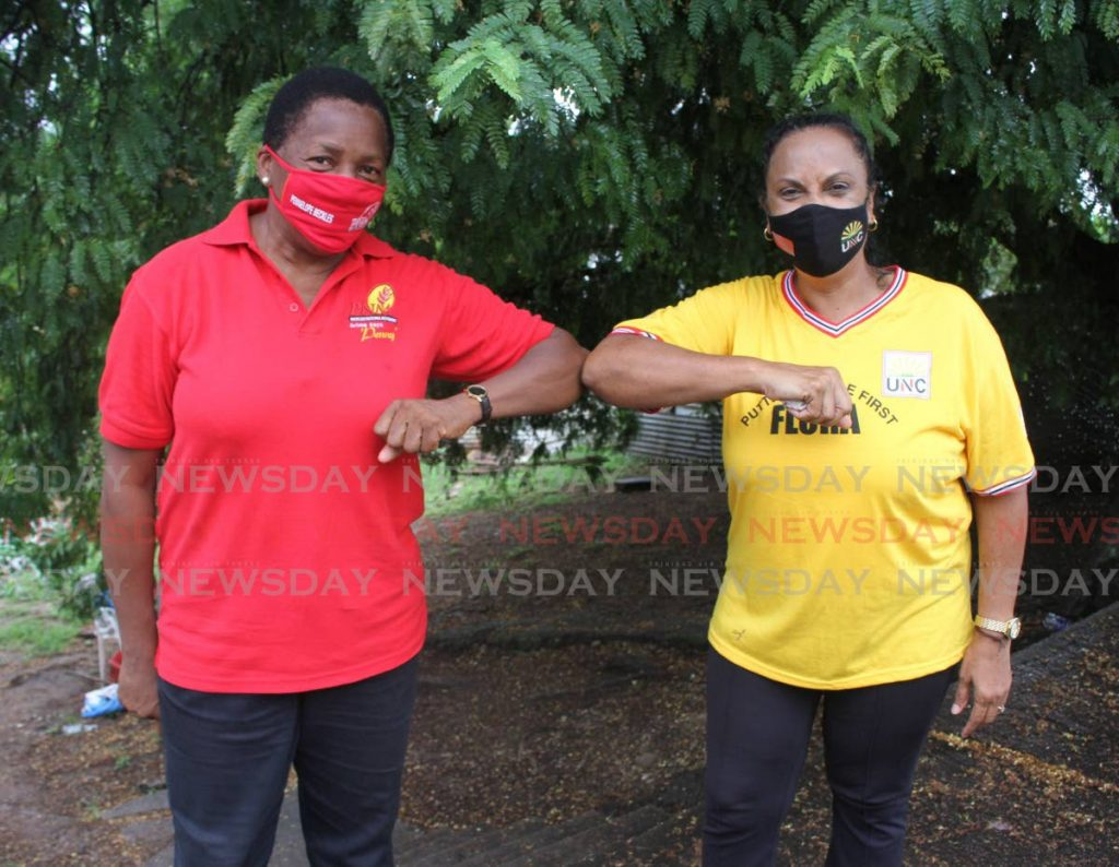 PNM's Penny Beckles-Robinson, left, and UNC's Flora Singh greet each other at Calvary Hill, Arima on Saturday. The Arima candidates went to help Michael Reyes whose house collapsed after heavy rainfall. -
