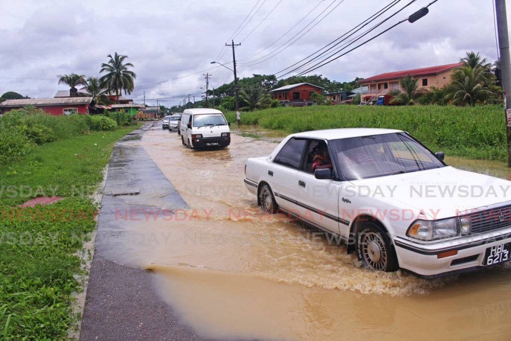 File photo: Drivers proceed cautiously through a flooded road in Barrackpore after heavy rainfall on August 9.  PHOTO BY CHEQUANA WHEELER