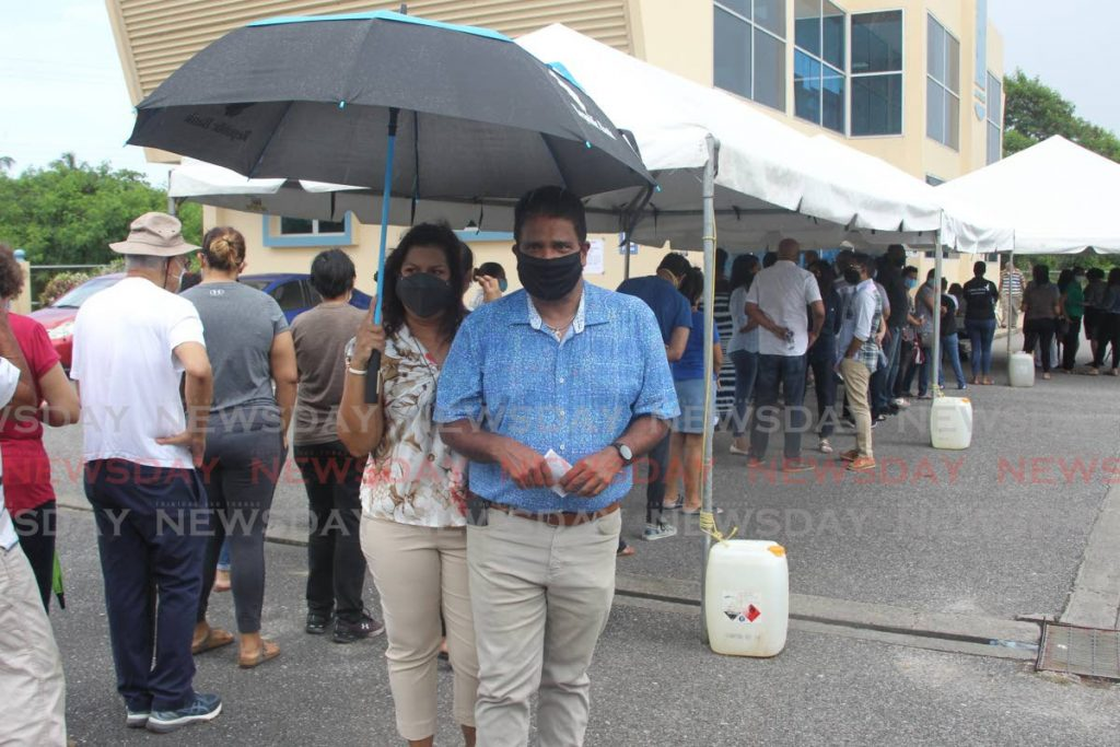 UNC Oropouche East candidate Dr Roodal Moonilal and his wife wait in line to vote at the Gulf View community centre. - LINCOLN HOLDER