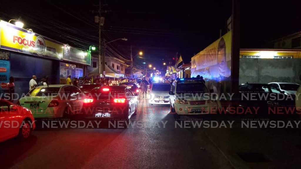 Police direct traffic and control the crowd as the UNC's Barataria/San Juan constituency headquarters on El Socorro Main Road, El Socorro on Monday night. - Roger Jacob