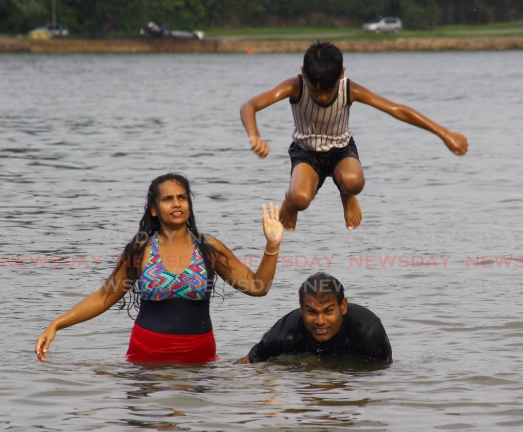 A family enjoys a fun day at Williams Bay, Chaguaramas on August 11. Due to the spike in covid19 cases, the Prime Minister on Saturday announced beaches, churches, gyms and other places will be closed once again from Monday. - ROGER JACOB