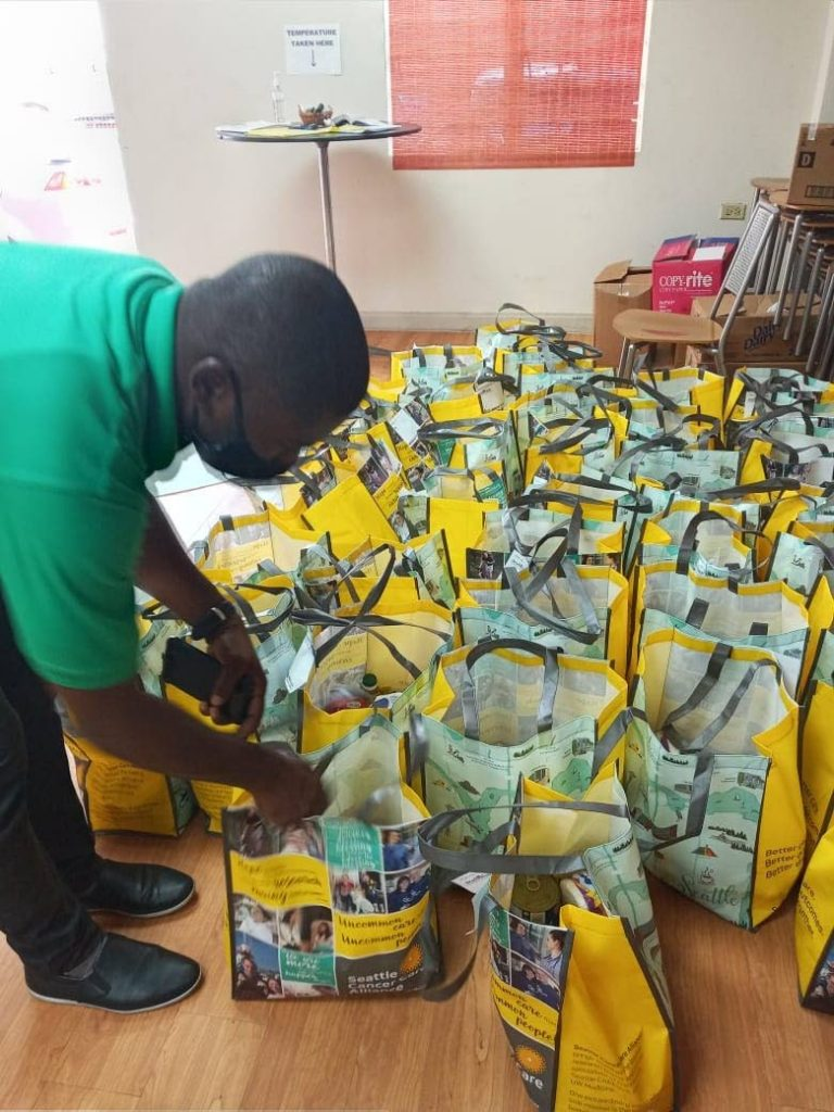 A GraceKennedy (TT) Limited employee sorts some of the  food hampers arranged by staff members for the Living Water Community. -