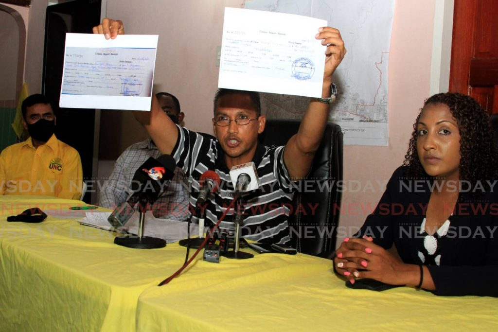 UNC St Joseph candidate Ahloy Hunt holds up a statement of poll during a press conference at the party's office in Tunapuna on Saturday. UNC PRO Anita Haynes, is at right, with other party officials at the table. - Ayanna Kinsale