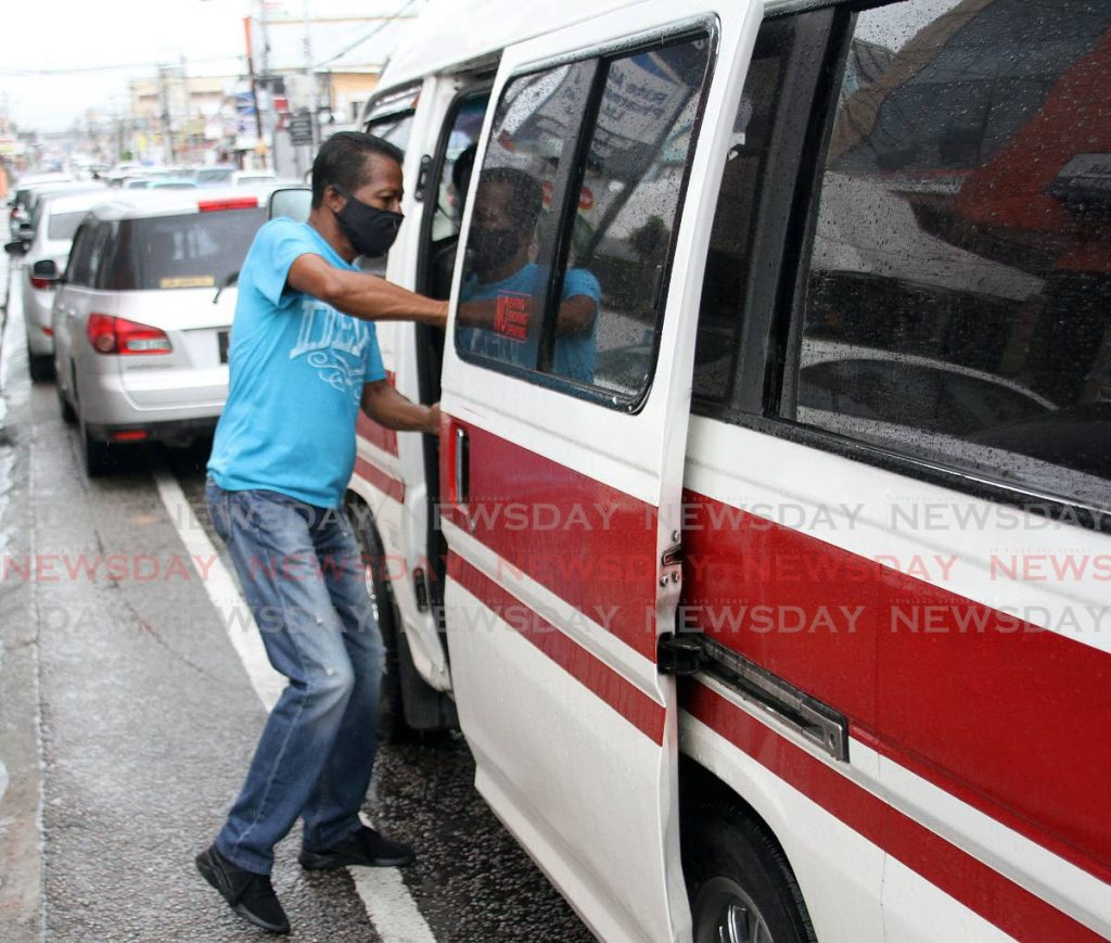 A masked passenger enters a maxi taxi in Tunapuna on August 17. Government is considering a request from maxi taxi operators to increase the number of passengers they can transport from 50 per cent to 65 per cent. - Angelo Marcelle