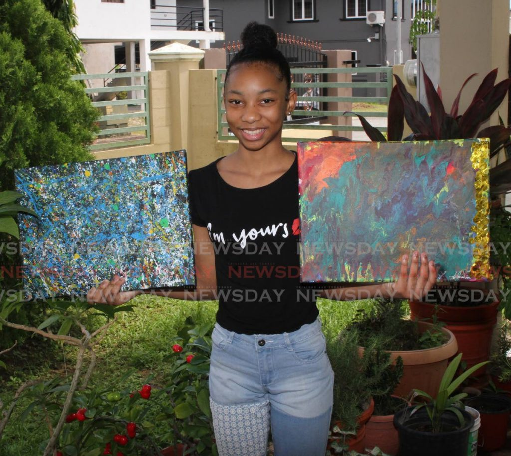 Azariah Gordon holds two of her favourite paintings, Dimanche Gras, left, and Majesty at her home in Couva. PHOTOS BY ANGELO MARCELLE -