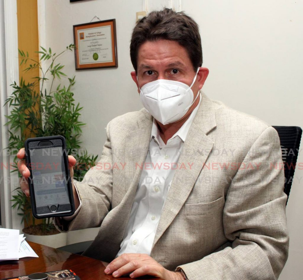 Energy Dynamics managing director Andre Escalante shows his ability to control air condition units remotely via his phone, at his Baden-Powell, Woodbrook office.  -